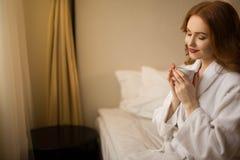 一件白色长袍的红发女孩有一杯咖啡的坐床 库存照片