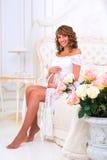 一件白色鞋带礼服的愉快的怀孕的女孩坐床在玫瑰附近 免版税库存照片