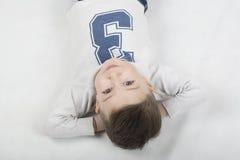 一件白色T恤杉和悬挂装置的时兴的男孩 免版税库存图片