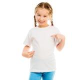 一件白色T恤杉和蓝色牛仔裤的逗人喜爱的小女孩 库存照片