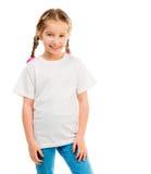 一件白色T恤杉和蓝色牛仔裤的逗人喜爱的小女孩 库存图片