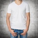 一件白色V字型T恤杉的年轻人,在口袋的手 库存图片