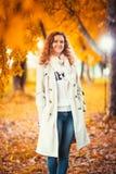 一件轻的外套的女孩在秋天公园背景  图库摄影