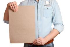 一件轻的牛仔布衬衣和深蓝牛仔裤的时髦的人拿着一个空白纸 免版税图库摄影