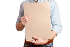 一件轻的牛仔布衬衣和深蓝牛仔裤的时髦的人拿着一个空白纸 库存照片