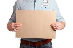 一件轻的牛仔布衬衣和深蓝牛仔裤的时髦的人拿着一个空白纸 免版税库存照片