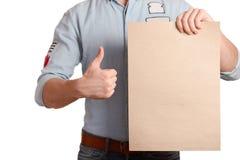 一件轻的牛仔布衬衣的时髦的人表明举行a的一个空白纸 库存图片