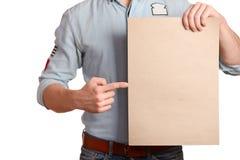 一件轻的牛仔布衬衣的时髦的人表明举行a的一个空白纸 免版税库存照片
