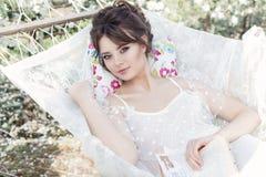 一件轻的白色礼服的美丽的性感的逗人喜爱的女孩在苹果开花的庭院在有书的吊床看见 免版税库存图片