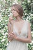 一件轻的礼服有精美构成的和头发的美丽的性感的女孩新娘在花园茉莉花 被称呼的照片fane艺术 免版税库存图片