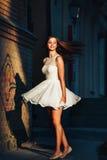 一件短的白色礼服的少妇在一条离开的街道上的一个舞蹈跳舞在墙壁背景 她跳舞象疯狂 免版税库存图片