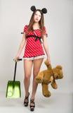 一件短的礼服的大乳房美丽的女孩有圆点的,熊在一只手上和在另一个玩具熊的一把铁锹 免版税图库摄影