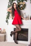 一件短的红色礼服的女孩在背景圣诞节装饰 图库摄影