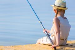 一件礼服和一个帽子的女孩有一根钓鱼竿的 免版税图库摄影
