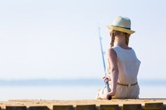 一件礼服和一个帽子的女孩有一根钓鱼竿的 图库摄影
