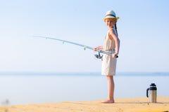 一件礼服和一个帽子的女孩有一根钓鱼竿的 免版税库存图片