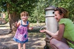 一件礼服的一个小迷人的女婴,有她的年轻母亲的,从一台罗马饮水器的喷口的饮用水在热的 图库摄影