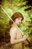 一件礼服的俏丽的女孩有户外葡萄酒剑的 图库摄影