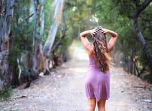一件礼服的女孩在朝前看的足迹 库存照片