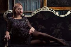 一件黑礼服的女孩在豪华屋子里 免版税图库摄影
