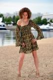 一件礼服的女孩有岸上绿色装饰品和卷发的 库存图片