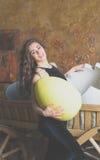 一件黑礼服的女孩用一个大鸡蛋在您的手上 免版税库存照片
