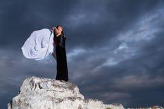 一件黑礼服的妇女在多云天空的背景 免版税库存图片