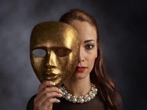 一件黑礼服的妇女有珍珠项链和老面具的 免版税库存图片