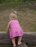 一件礼服的小女孩在木日志 免版税库存图片