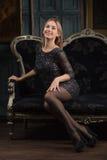 一件黑礼服的微笑的女孩在豪华屋子 免版税图库摄影