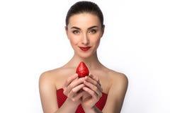 一件礼服的美丽的女孩有完善的微笑的吃红色草莓的 画象裸体构成 健康的食物 查出 免版税图库摄影