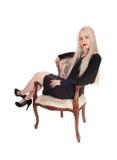 一件黑礼服的美丽的妇女在扶手椅子 库存照片