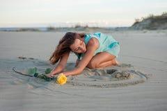一件礼服的美丽的妇女有在海滩的一朵黄色玫瑰的 免版税库存图片