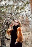 一件黑礼服的美丽的妇女有在他的胳膊的一头猫头鹰的 有长的头发的金发碧眼的女人本质上拿着猫头鹰的 浪漫精美女孩 库存图片