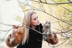 一件黑礼服的美丽的妇女有在他的胳膊的一头猫头鹰的 有长的头发的金发碧眼的女人本质上拿着猫头鹰的 浪漫精美女孩 图库摄影
