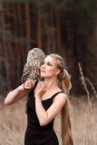 一件黑礼服的美丽的妇女有在他的胳膊的一头猫头鹰的 有长的头发的金发碧眼的女人本质上拿着猫头鹰的 浪漫精美女孩 库存照片