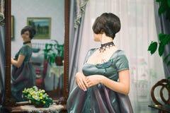 一件礼服的美丽的少妇在减速火箭的样式画象 在葡萄酒的时髦衣物 免版税库存图片