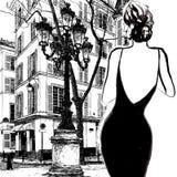 一件黑礼服的年轻端庄的妇女 免版税库存照片