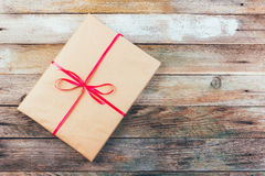 一件礼物在包装纸和栓与在木减速火箭的难看的东西背景的一条红色丝带 库存图片