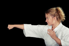 一件年轻空手道妇女佩带的和服的外形在武术姿势的 免版税图库摄影