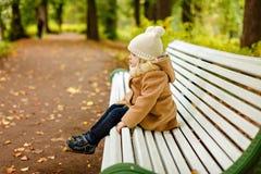 一件米黄外套的小俏丽的女孩坐长凳和哀伤在 免版税库存照片