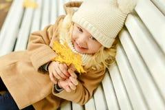 一件米黄外套的小俏丽的女孩坐长凳和laughi 免版税库存照片