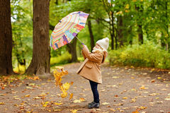 一件米黄外套的小俏丽的女孩,在公园投掷的秋天 免版税库存照片