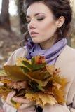 一件米黄外套的美丽的深色的妇女走在秋天公园的在与色的秋天花束的一多云天离开,树荫 免版税库存照片
