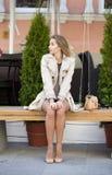 一件米黄外套的年轻美丽的女孩坐在s的一条长凳 免版税图库摄影