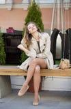 一件米黄外套的年轻美丽的女孩坐在s的一条长凳 免版税库存照片