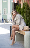 一件米黄外套的年轻美丽的女孩坐在s的一条长凳 库存照片