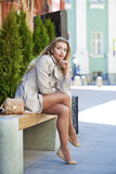 一件米黄外套的年轻美丽的女孩坐在s的一条长凳 库存图片