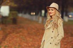 一件米黄帽子和外套的年轻美丽的女孩在一个公园在秋天 库存图片