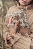 一件米黄毛线衣的美丽的哀伤的逗人喜爱的可爱的妇女宽在干草的领域在一冷的秋天多云天,拿着一副干燥胸罩 免版税库存照片